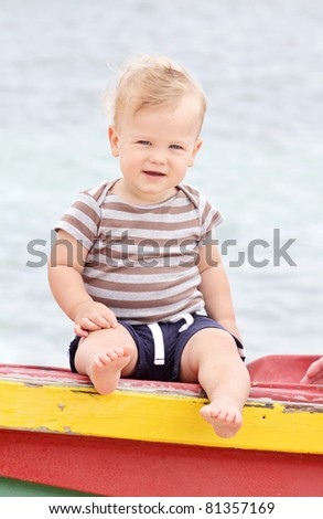 Baby or toddler boy sitting on a colorful tropical boat against the ocean - stock photo