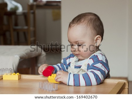 Baby or toddler child playing with plastic blocks at home.  - stock photo