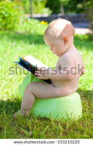 baby outdoors is sitting on his potty and reading his book