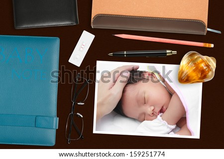 baby photo with paperweight & pregnancy test on the desk - stock photo