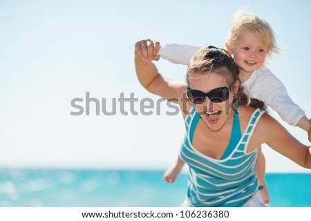 Baby piggybacking mother on beach - stock photo