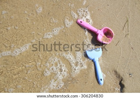 Baby pink shovel on the shore of the estuary. The waves and sand on the beach. - stock photo