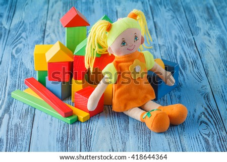 Baby play concept, cloth doll and wooden building blocks for play - stock photo