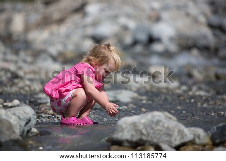 Baby playing by a creek - stock photo