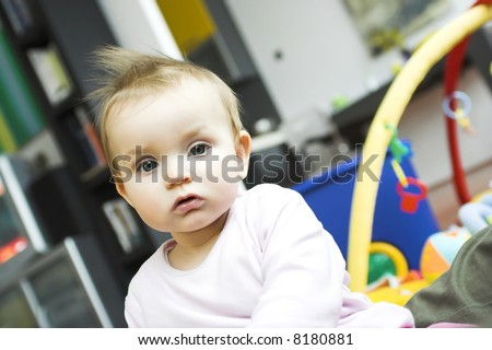 baby playing in a bedroom - calm face expression
