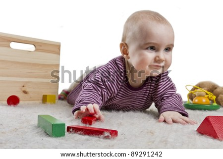 baby playing on floor with toys around