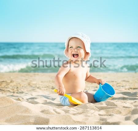 Baby playing on the sandy beach near the sea - stock photo