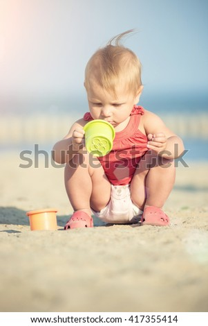 Baby playing on the sandy beach near the sea. Cute little girl in red dress with sand on tropical beach. Ocean coast. - stock photo