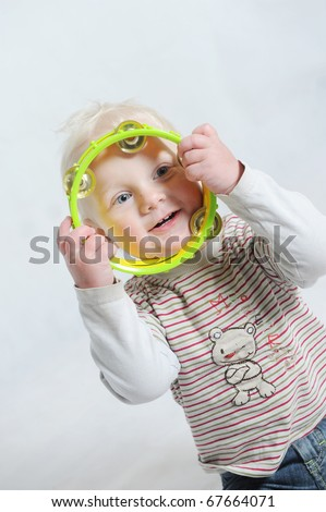 baby playing tambourine - stock photo