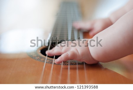 Baby playing the guitar - stock photo