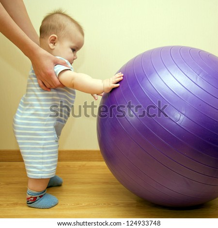 Baby playing with a big gymnastic ball. Mother helping and supporting kid. - stock photo