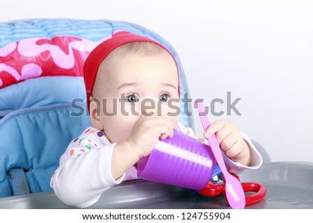 Baby playing with a cup and spoon - stock photo