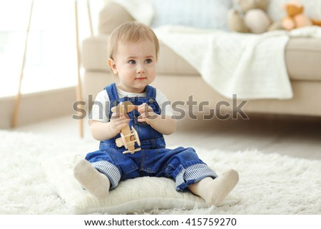 Baby playing with a toy helicopter on the floor - stock photo