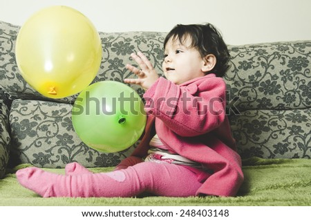 Baby Playing with balloon at home sofa - stock photo