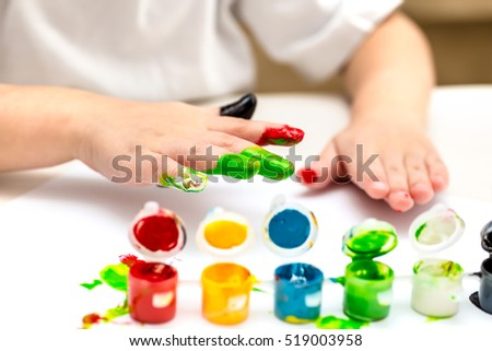 baby playing with colorful paints at home at the table