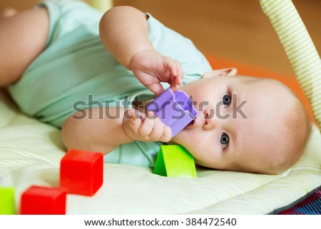 Baby playing with colorful toys - stock photo