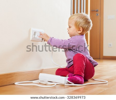 Baby playing with electrical extension and outlet on floor at home