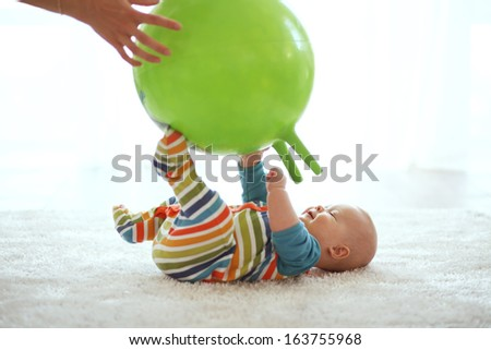 Baby playing with gymnastic ball with mother at home - stock photo