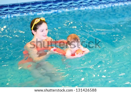 Baby playing with her mother in an early swimming class - stock photo