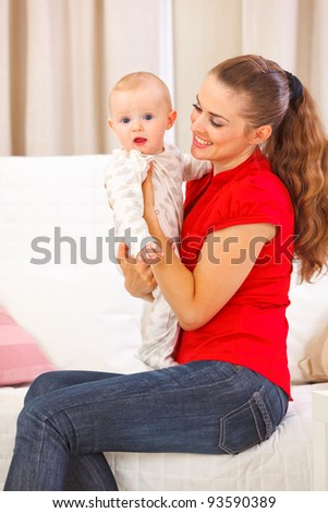 Baby playing with mother on divan