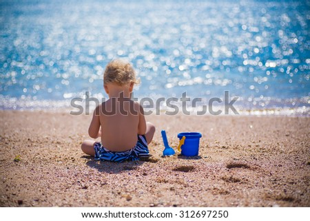 baby playing with sand on sea shore - stock photo