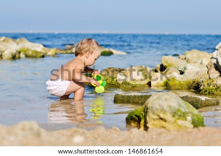 baby playing with water in sea - stock photo
