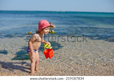 baby playing with water on the beach - stock photo