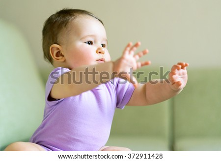 Baby plays and doing gymnastics at home - stock photo