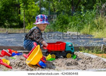 baby plays in sandbox - stock photo