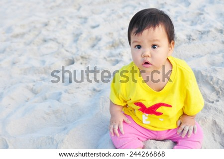 baby plays sand on beach - stock photo