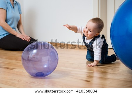 Baby plays with inflatable ball at home on floor, mother in background