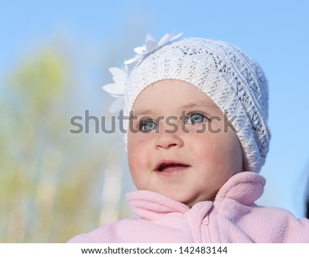 Baby portrait in a white cap against the sky