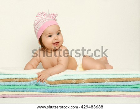 baby portrait in diaper on towel at studio, yellow toned background - stock photo