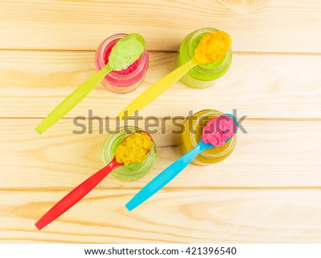 Baby puree in jars and spoons on a background of light wood. View from above.