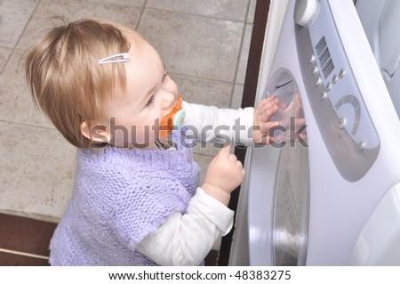 baby puts linen in washing machine - stock photo