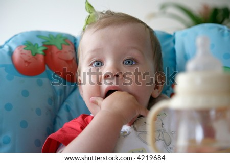baby putting hand in mouth - stock photo
