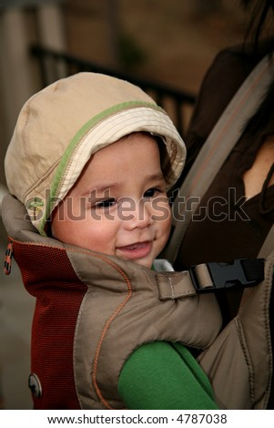 Baby riding in a front carrier - stock photo