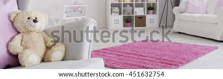 Baby room in pink and white, teddy bear sitting on an armchair - stock photo