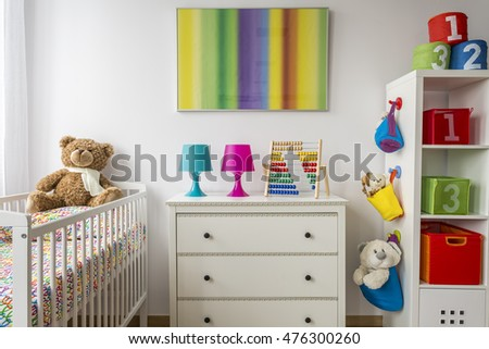 Baby room with a commode, cradle and rack with colorful boxes