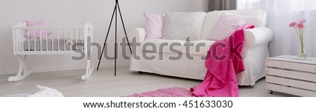 Baby room with white creadle and comfortable sofa - stock photo