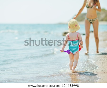 Baby running to mother along seashore - stock photo