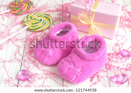 baby's bootees and gift box on wooden background