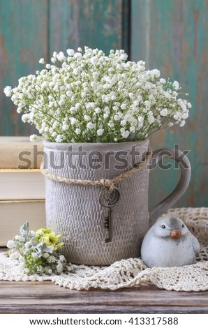 Baby's breath (gypsophila paniculata) in grey ceramic vase on wooden background - stock photo
