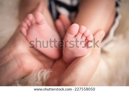 "Baby's feet in mother's hand. newborn baby feet on female hands. Baby feet on white coverlet. Toes. Feet how a heart or ""V"". Horizontal photo. Macro. Close-up. - stock photo"