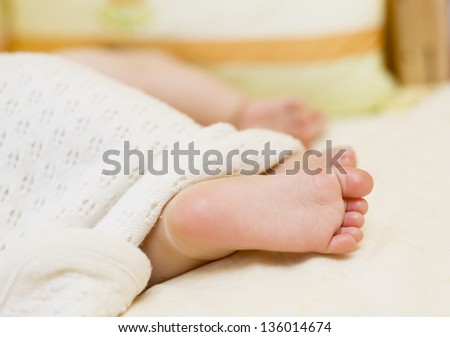 Baby`s feet on a white sheet