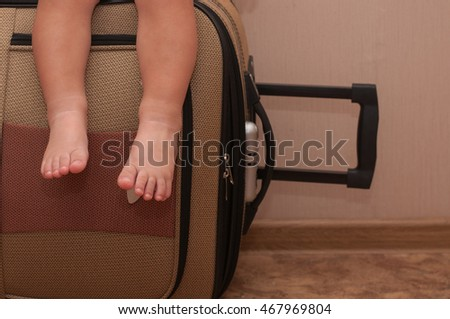 Baby's feet on the background suitcase