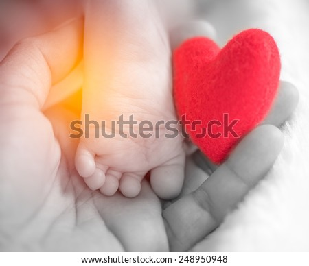 baby's feet with a red heart in vintage filter effect - stock photo