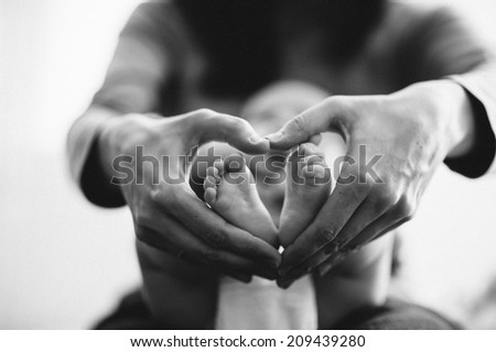 Baby's foot in mother hands closeup - stock photo