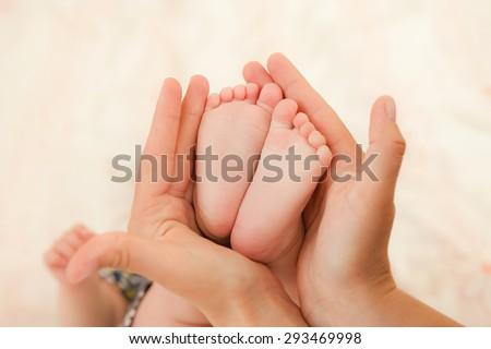 Baby's foot in mother hands closeup - stock photo