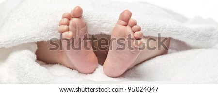baby's foot under towel closeup isolated on white